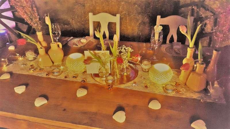 Holztisch mit Vasen, Blumen und zwei Gedecken.