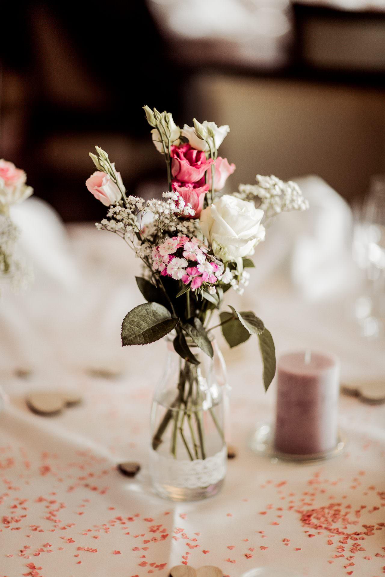 Glas mit Blumen auf einem Tisch.