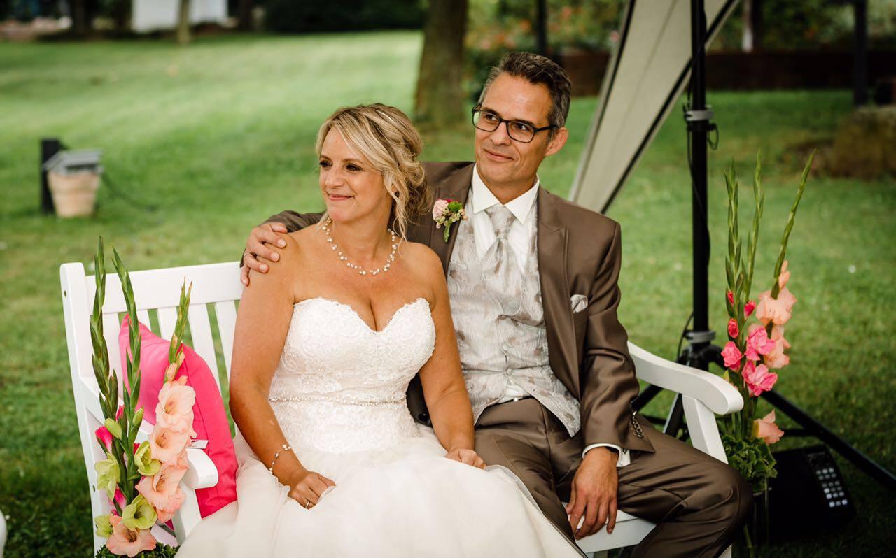 Sandra & Ralf in Hochzeitskleidung auf einer weißen Bank