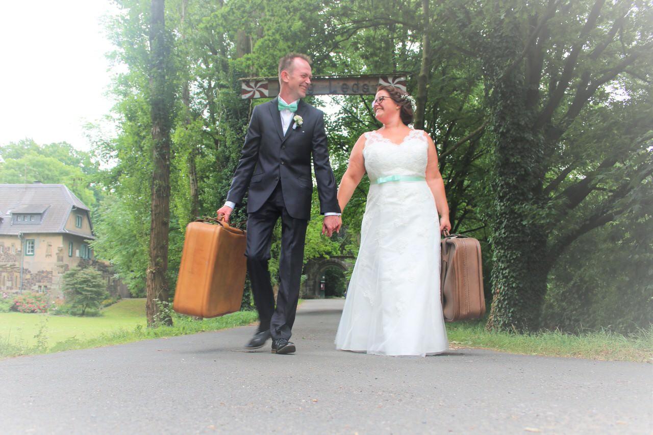 Stefanie & Dieter mit Koffern vor dem Burgtor