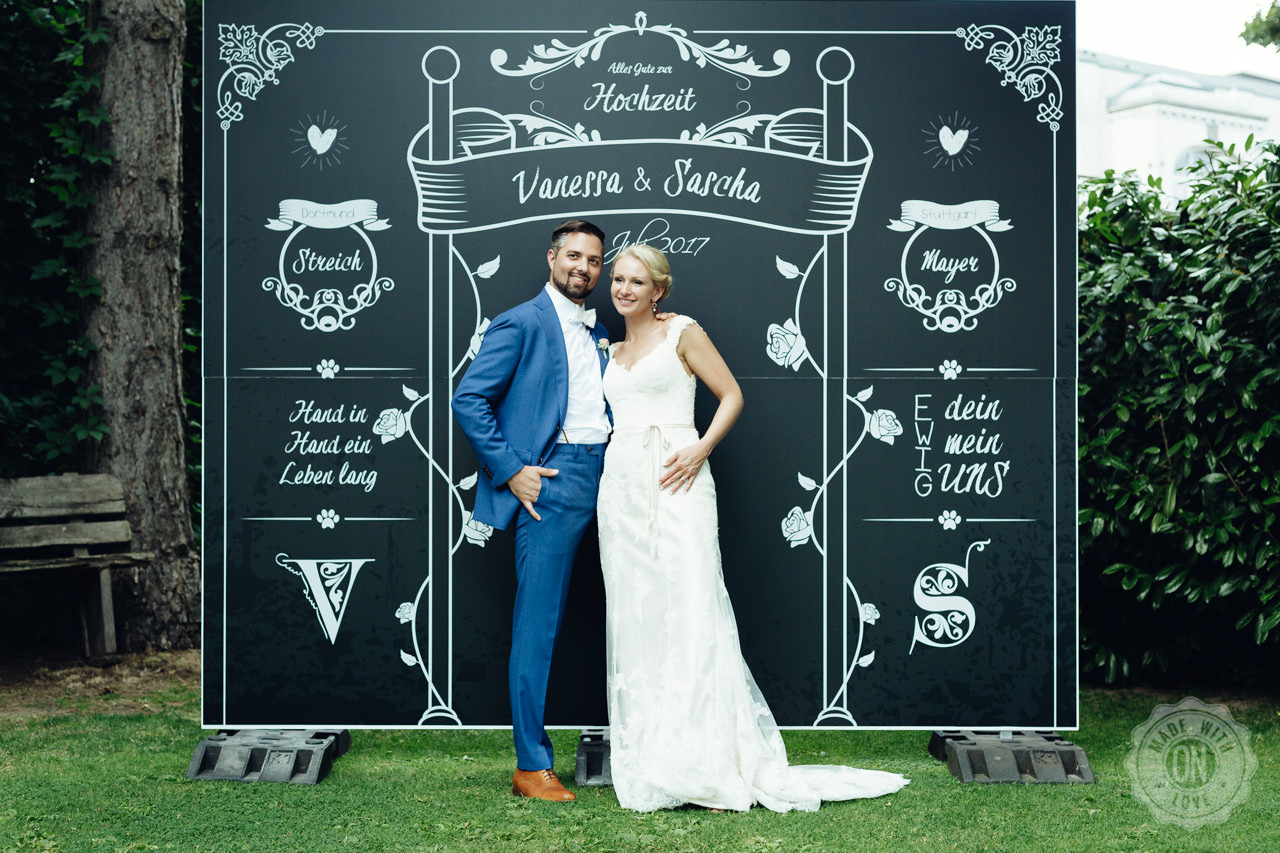 Vanessa & Sascha vor einer großen Tafel mit den Daten ihrer Hochzeit