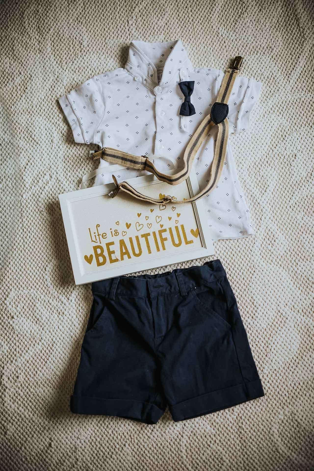Hemd, Fliege, Hosenträger und kurze Hose liegen für einen Jungen bereit.