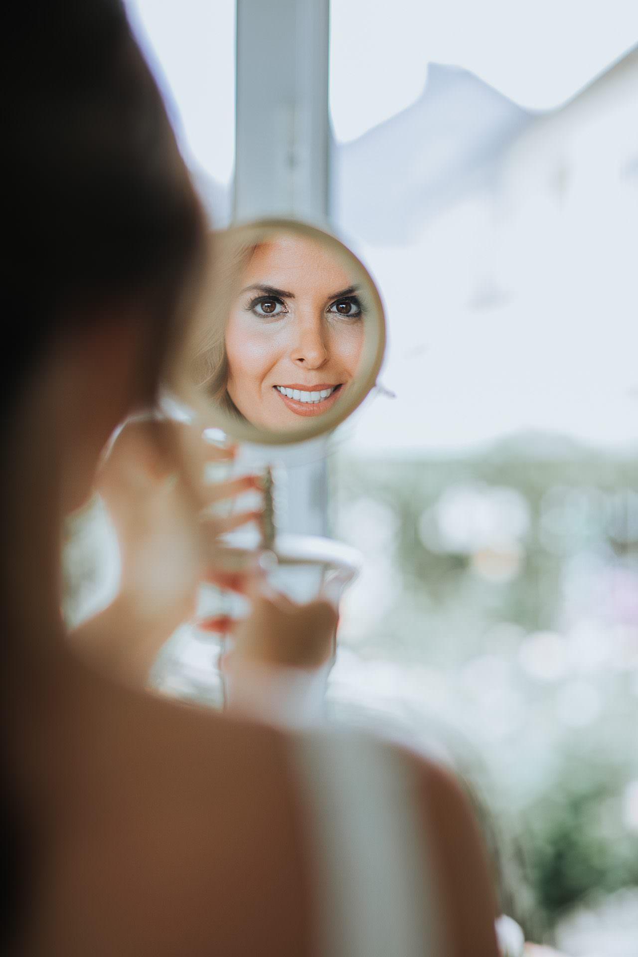 Janine schaut in den Fotografen in einem Handspiegel an