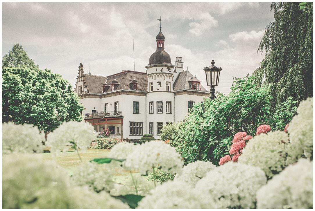 Blick durch Blumen auf das Herrenhaus von Gut Nettehammer
