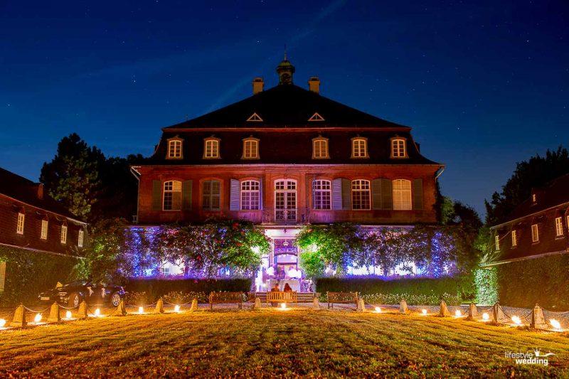 Das Schloss zu Beginn der Nacht mit beleuchteter Veranda und Fackeln im Schlosshof