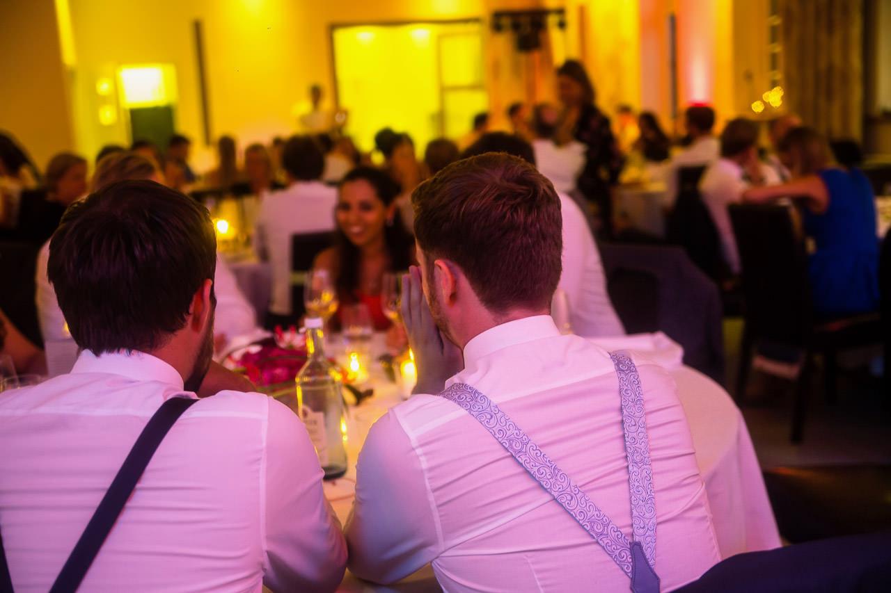 Zwei Männer im weißen Hemd mit Hosenträgern am Tisch
