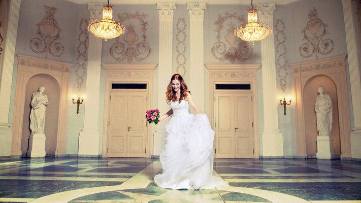 Braut mit Hochzeitsstrauß im leeren Beethovensaal der Redoute