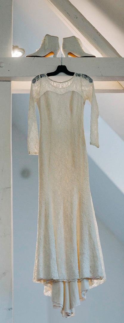 Nataschas Hochzeitskleid hängt an einem weißen Balken. Auf diesem stehen die passenden weißen Stiefeletten, die sie später trägt.